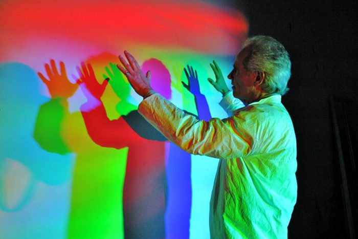Man making multiple colored rainbow shadows of himself on a screen