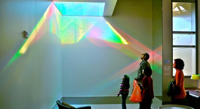 viewers examine solar skylight of Library Rainbow Art Installation