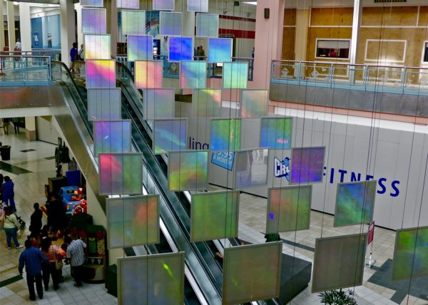 "52, 36"" x 36"" suspended, glowing, colorful rainbow prism panels hang suspended in this light art installation"